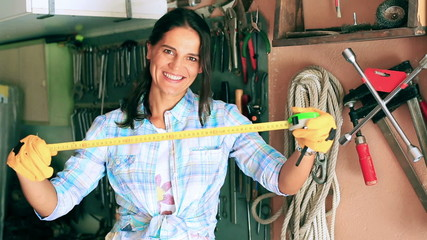 Happy woman showing tape measure to the camera in her garage