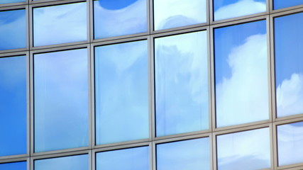 Timelapse of clouds in windows of office building.  Find similar