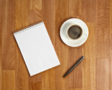 Fototapety Blank notepad with office supplies and cup of coffee on wooden t