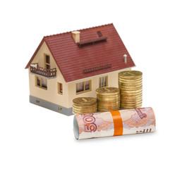 Монет и сверток купюр на фоне дома