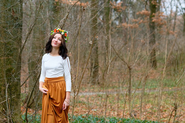 Girl with flower wreath on her head in the autumn forest