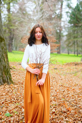Young girl with dry twigs in her hand autumn outdoors