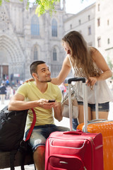 smiling young couple using phone navigating system