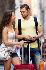 Happy  young travellers finding path with phone