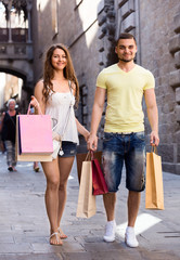 Smiling young loving couple with bags at city