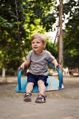 Happy little boy swinging on a swing