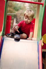 Young Boy Playing with Toy Car on Slide