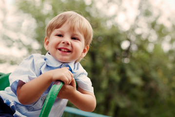 Young Smiling Boy Sitting Outdoors on Playground