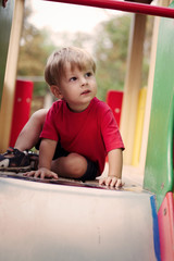 Young Boy Sitting at Top of Slide