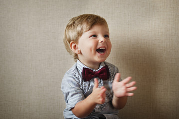 Beautiful little boy laughing and clapping