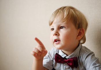 Young Boy Wearing Bow Tie and Pointing to the Side