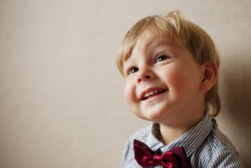 Young Boy Wearing Bow Tie Smiling and Looking Up