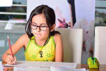 Little cute girl doing homework at home