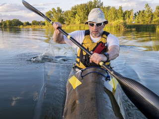 senior male paddler training in a fast sea kayak