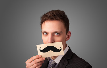 Happy businessman holding funny mustache card on his mouth