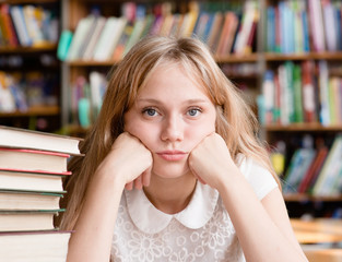 Sad female student in library looking at camera