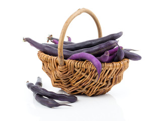 Red bean pods in wicker basket over white background