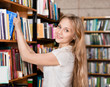 happy student in the library surrounded by books