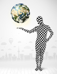 man in full body suit holding planet earth
