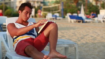 attractive young man reading a book on the beach