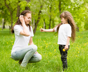 the daughter gives to mother a dandelion
