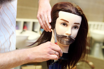 Barber student trimming brown hair using puppet and scissors