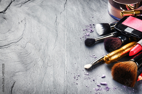 Various makeup products on dark background - 69533128