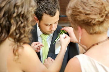 Pinning boutonniere flowers to the groom before wedding ceremony