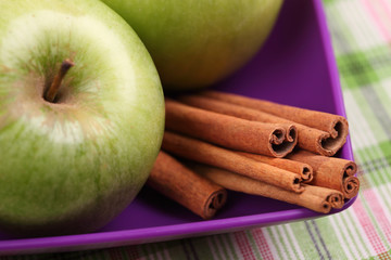 Apples and cinnamon sticks in a bowl