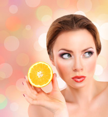 Beautiful young woman with bright make-up holding orange