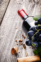 Bottle of red wine with fresh grape and corkscrew