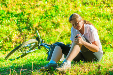 cyclist holds a his bruised knee while sitting on the lawn