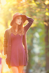 Redhead girl in hat in the autumn park.