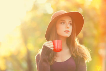 Beautiful redhead girl with cup in the park.