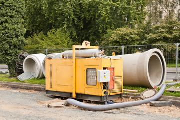 Kanalbauarbeiten - Ein Stromerzeuger steht vor Rohren aus Beton