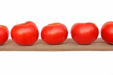 Five tomatoes on wooden plank