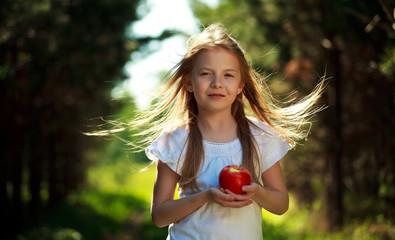 Pretty little girl holding the apple