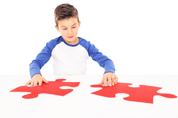 Boy connecting two huge pieces of a puzzle