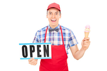 Excited ice cream vendor holding an open sign