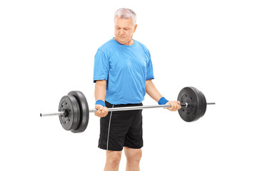 Mature man exercising with a heavy barbell