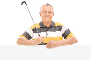 Mature golf player standing behind a panel
