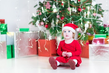 Cute little toddler girl in a santa hat and red dress playing wi