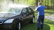 Worker wash black car outdoor with high pressure water equipment