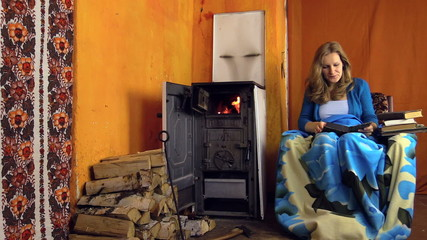 young girl found interesting book and read near to the stove