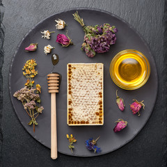 Honey and dried herbs on dark background