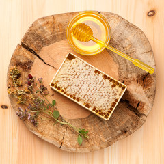 Honey, honey comb and dried herbs on wooden board