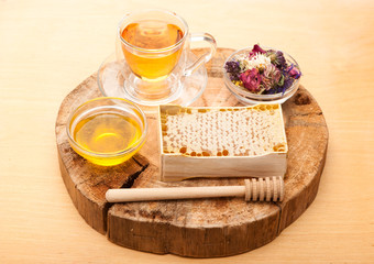 Honey comb, herbal tea and dried herbs on wooden board