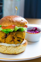 Vegan burger with beans and tofu served with sugar beet cream