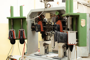 Machine with clamps for unfinished shoes