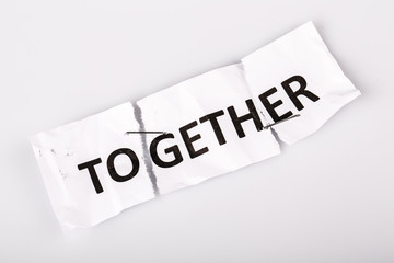 """TOGETHER"" word written on torn and stapled paper"